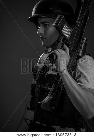 Airsoft, paintball sport player wearing protective helmet aiming pistol ,black armor and machine gun
