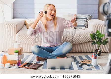 Happy young woman is recording video for blog at home. She is applying blush on her cheek and smiling