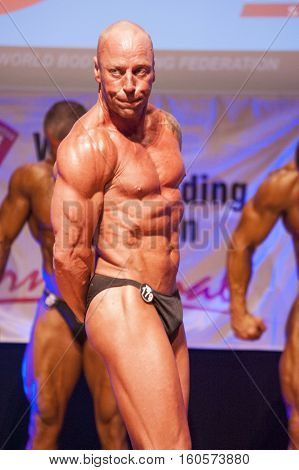 MAASTRICHT THE NETHERLANDS - OCTOBER 25 2015: Male bodybuilder Erik Stobbe flexes his muscles and shows his best physique in a triceps pose on stage at the World Grandprix Bodybuilding and Fitness of the WBBF-WFF