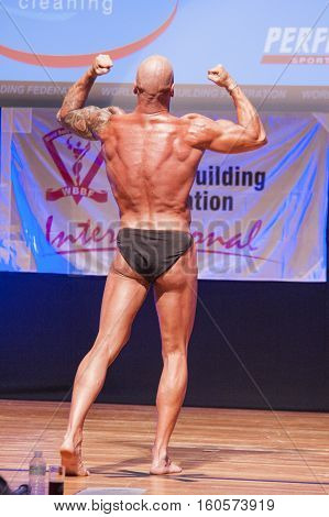 MAASTRICHT THE NETHERLANDS - OCTOBER 25 2015: Male bodybuilder Erik Stobbe flexes his muscles and shows his best physique in a back double biceps pose on stage at the World Grandprix Bodybuilding and Fitness of the WBBF-WFF
