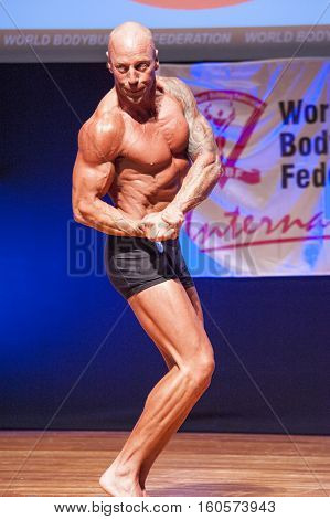 MAASTRICHT THE NETHERLANDS - OCTOBER 25 2015: Male bodybuilder Erik Stobbe shows his best chest pose at the World Grandprix Bodybuilding and Fitness of the WBBF-WFF