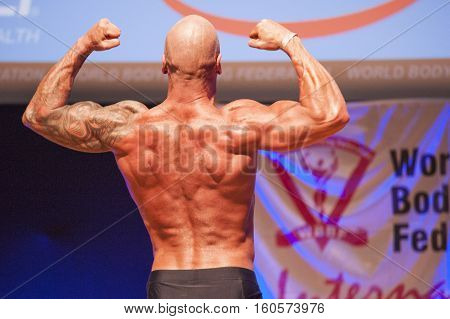 MAASTRICHT THE NETHERLANDS - OCTOBER 25 2015: Male bodybuilder Erik Stobbe shows his best back double biceps pose at the World Grandprix Bodybuilding and Fitness of the WBBF-WFF