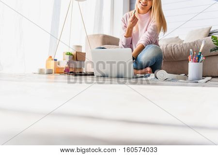 Happy young woman is maintaining fashion blog in internet. She is holding lipstick and laughing. Law angle of floor with copy space
