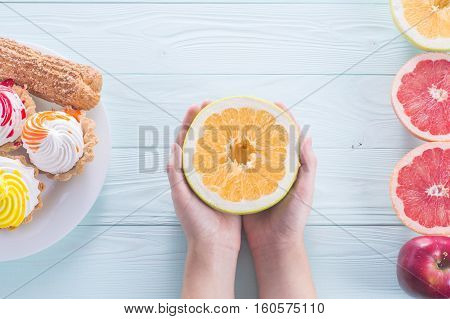 Hands of a young woman holding a grapefruit sweetie. Woman making a choice between sweets and fruits made a choice in favor of fruits and holding an oroblanco. Weight Loss. Unhealthy vs healthy food top view.