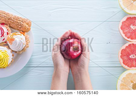 Hands of a young woman holding a red apple. Woman making a choice between sweets and fruits made a choice in favor of fruits and holding an apple. Weight Loss. Unhealthy vs healthy food top view.