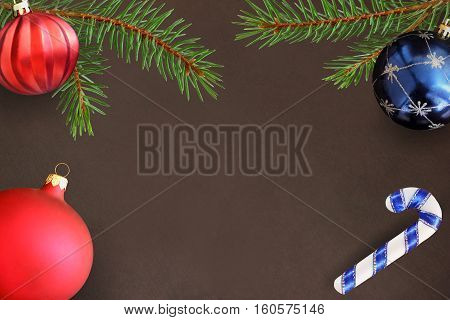 Dark background with Christmas fir branch stick red wavy dull and blue ball