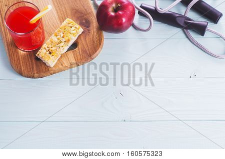 The concept of weight loss jump rope juice cereal bar and red apple top view. Healthy lifestyle. Fitness Background with copy space. Sport and diet.