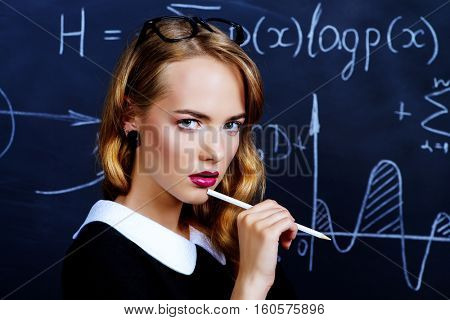 Pretty student girl in strict black dress standing by a black school board. Beauty, fashion. Education, college.