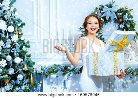 Christmas, winter holidays concept. Beautiful charming woman in evening dress opens a gift box and surprises. Luxurious apartments decorated for Christmas. Beauty, fashion.