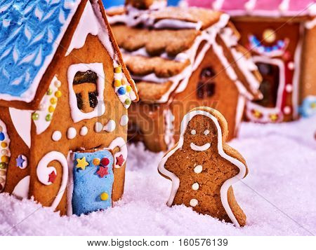 Street consisting of gingerbread houses, close-up. Joyful Gingerbread man in the snow. Merry Christmas.