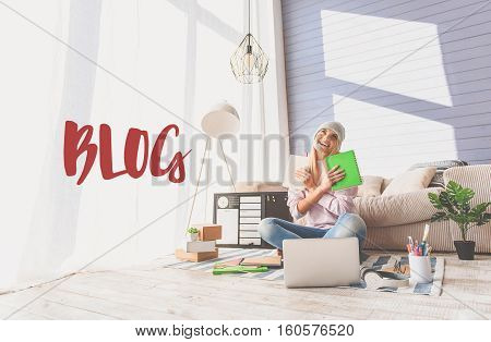 Blog. Happy young female blogger is carrying notebooks and hugging it with admiration. Girl is sitting at home and laughing