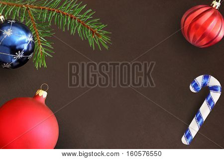 Dark background with Christmas fir branch stick blue and red wavy dull ball