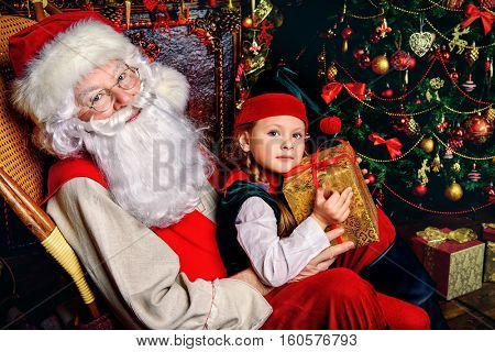 Santa Claus and the elf girl with gift box. Miracles on Christmas.