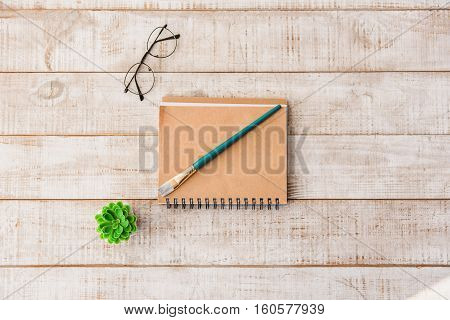 Top view close-up of brush on notebook, small flowerpot, eyeglasses on wooden desk