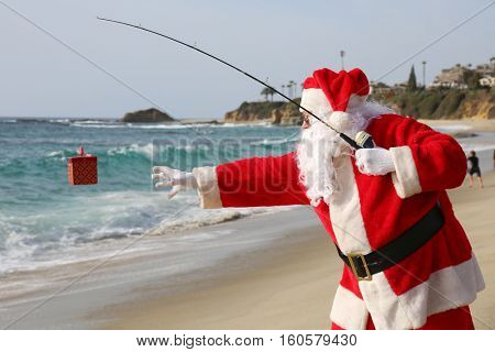 Christmas Santa Claus Fishing for Xmas Presents with his Fishing Pole. Santa Catches a present while fishing.