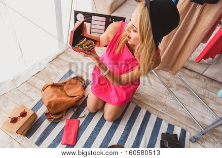 Top view of fashion blogger opening jewelry box. Girl is sitting on floor and looking at bracelet with shock