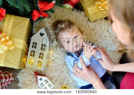 Cute Portrait Of Little Baby Celebrates Christmas. New Year's Holidays. Boy In Boytie Lies Under The