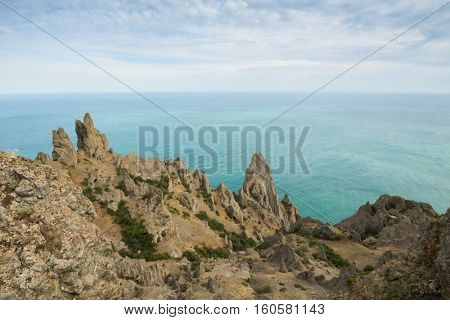 Rocks near sea waterside, skyline and blue water at summer day