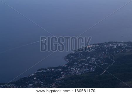 Small resort town near sea shore, ship sails with trace at summer evening