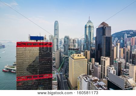Residential buildings and modern office buildings on shore near mountain in Hong Kong, China, view from China Merchants Tower