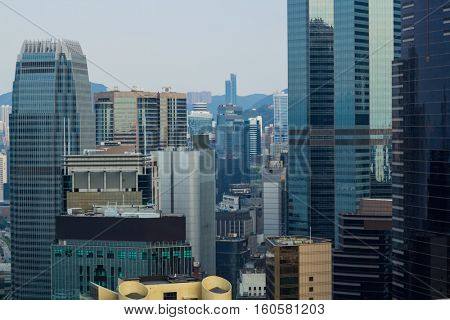 Tall office glass buildings and roofs in city in Hong Kong, China, view from China Merchants Tower
