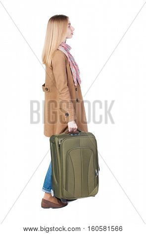 Back view of woman with suitcase looking up. Standing young girl. Rear view people collection. Isolated over background. Pretty girl in a striped dress stands with a suitcase and looking at something