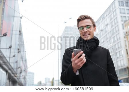 From below image of business man in glasses with phone on the street