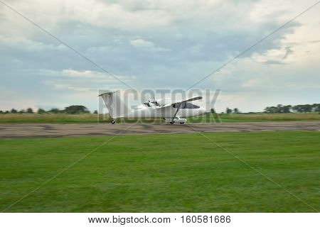 Kiev Region Ukraine - July 19 2014: Light private twin-engine plane is taking off from the runway with stormy sky on sunset on the background. Blurry background due to using panning while shooting at long exposure