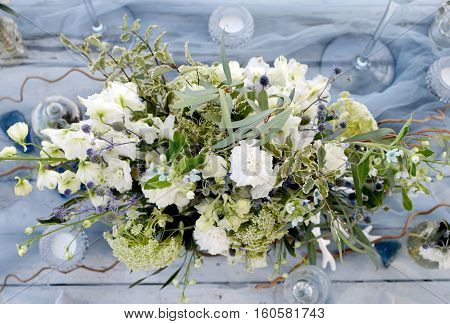 able decorated with a bouquet of white roses blue flowers