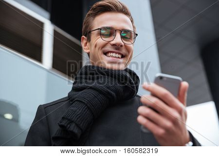 From below portrait of business man with phone on the street