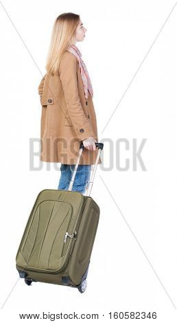 Back view of woman with suitcase looking up. Standing young girl. Rear view people collection.  Pretty girl in a striped dress stands with a suitcase and looking at something