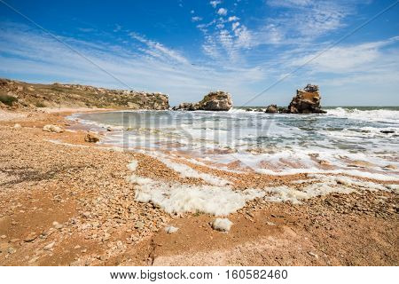 Waterside of sea with beach, cloudy sky and rocks at summer sunny day