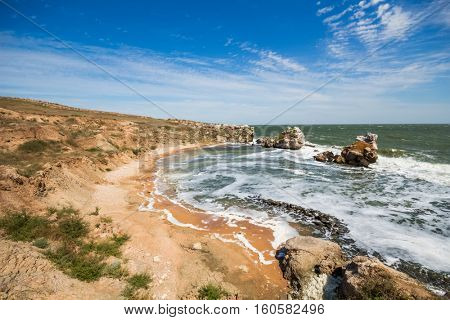 Shore front of sea with beach, cloudy sky and rocks at summer sunny day