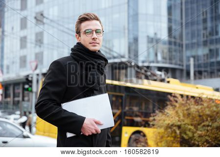 Young handsome Business man in glasses and warm clothes holding folder in hand and standing sideways on the street as well as looking at camera