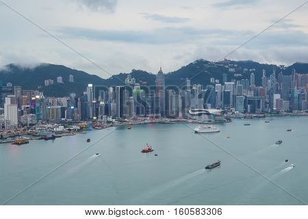 Skyscrapers on sea shore in business area, ships at cloudy day in Hong Kong, China, view from Harbourfront center