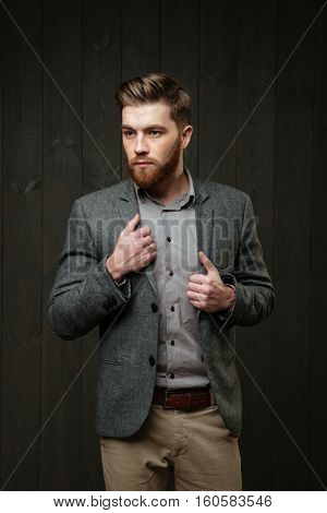 Portrait of a serious bearded man in casual suit standing and looking away isolated on the black wooden background
