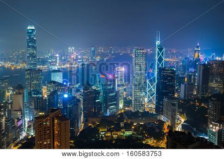 Night city with illumination in mist and sea coast in Hong Kong, China, view from Queen Garden