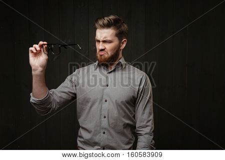 Portrait of a bearded unsatisfied disgusted man in shirt looking at eyeglasses isolated on the black wooden background