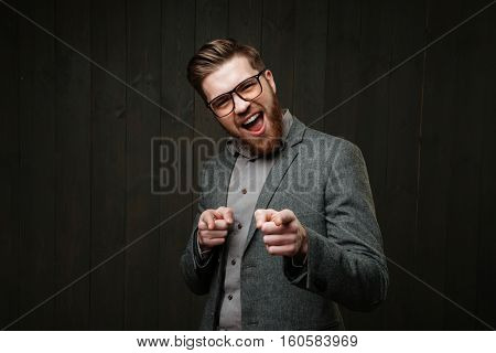 Portrait of an excited bearded man in eyeglasses pointing fingers at camera