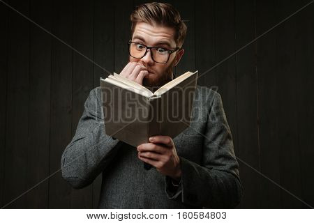 Portrait of a nervous man in eyeglasses reading book and biting nails isolated on the black wooden background