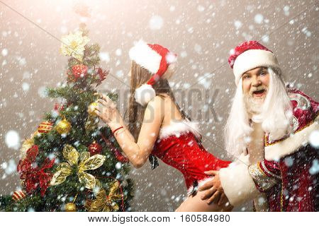 Funny santa claus man in new year suit grabs pretty sexy girl decorating Christmas tree on grey wall