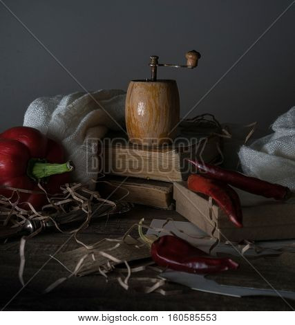 vintage. red pepper, mill, and a towel on a wooden table.