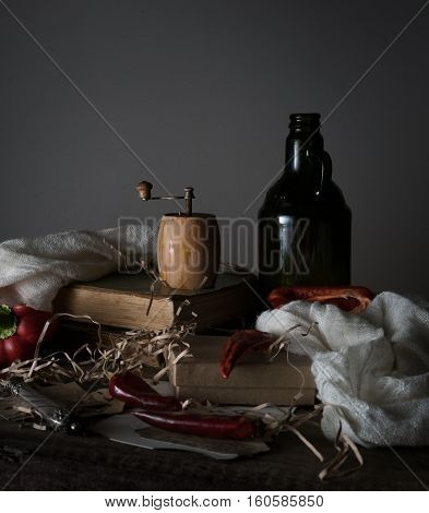 vintage. old bottle with oil, red pepper, mill, and a towel on a wooden table.