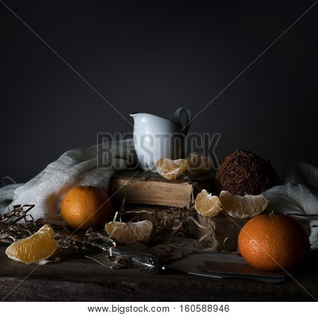 vintage. tangerines, tangerine slices, milk, scarf and old silver knife on a wooden table.
