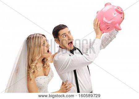 Shocked newlywed couple shaking an empty piggybank isolated on white background