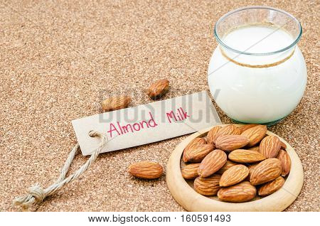 Almond and almond milk in glass with almond tag on wood background.