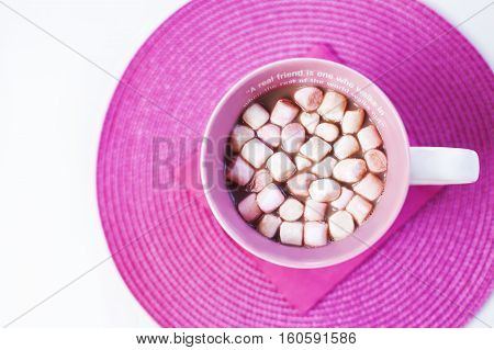 Cup of hot chocolate with sweet marshmallows on a pink placement with pink napkin. A friendship quote painted on the cup. Natural light. Isolated on white. Flat lay.