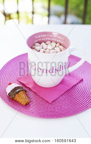 Cup of hot chocolate with sweet marshmallows on a pink placement with ice cream cone magnet. A friendship quote painted on the cup. Natural light. White table in the garden