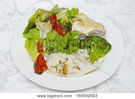 Meat with vegetables on the white plate on the table