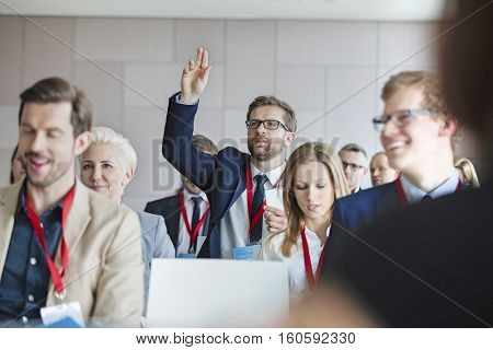 Businessman asking questions during seminar